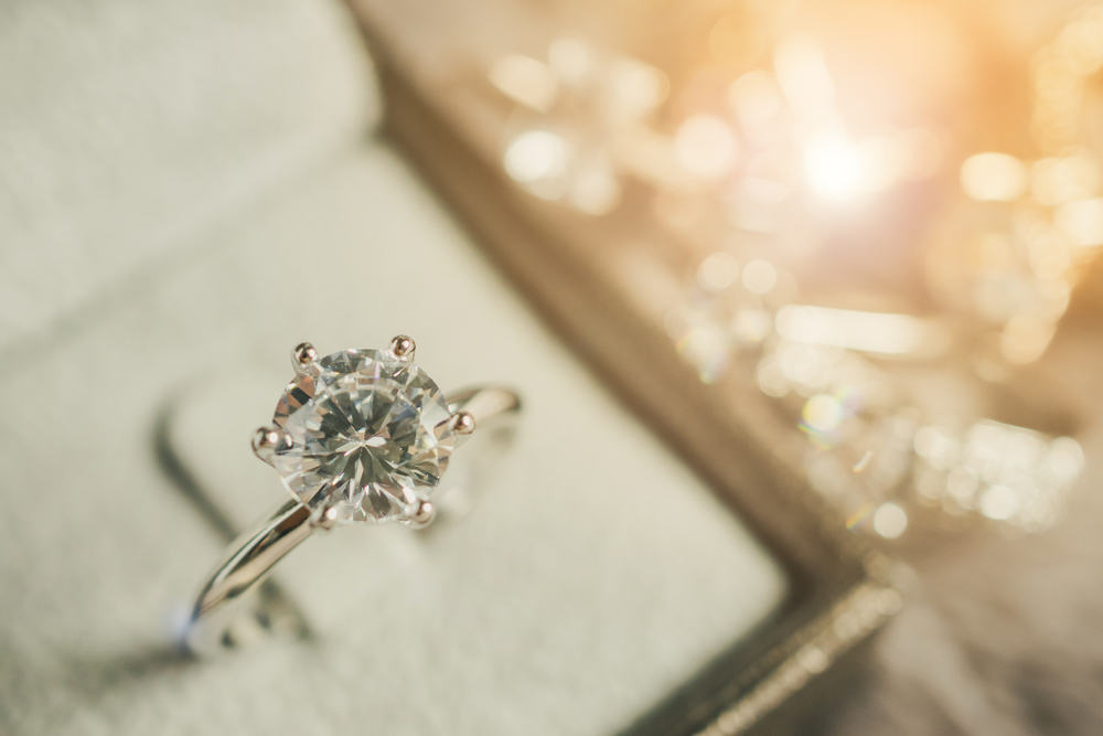 A diamond ring on a table  Description automatically generated with low confidence